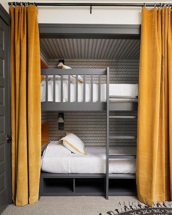 grey bunk beds with a mathcing ladder and storage psace under the bed, mustard curtains and wall lamps over the beds