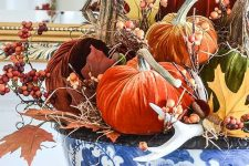 lots of bright velvet pumpkins, berries, antlers and faux leaves in a blue handpainted bowl for a bold centerpiece