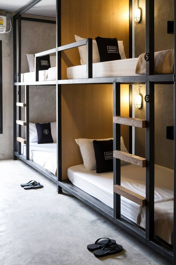 stylish industrial bunk beds of metal and wood, with wall lamps and ladders to reach each upper bed