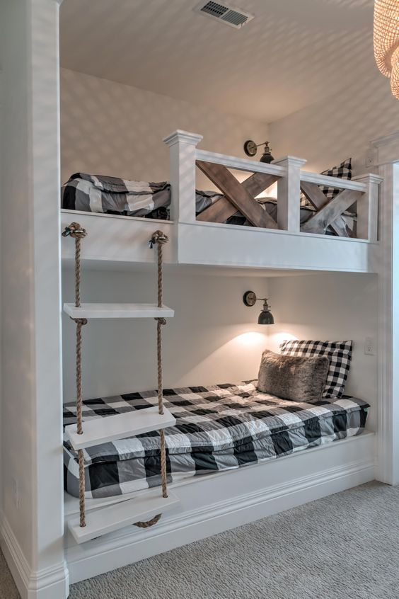 vintage rustic bunk beds with a rope ladder, wall lamps and stained wood railing for safety
