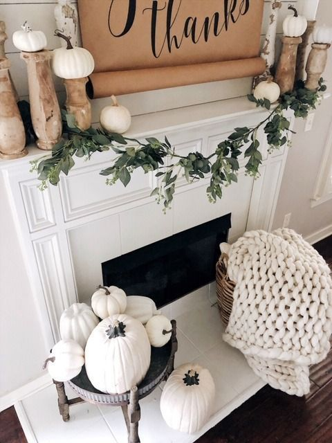 white pumpkins on vintage wooden stands and a dark wooden stand with lots of white pumpkins by the fireplace