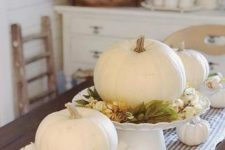 white pumpkins with fall leaves and berries plus some white pumpkins on the table for a centerpiece