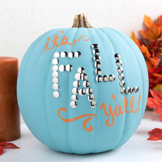 a blue pumpkin decorated with orange letters and some decorative nails for fall and Thanksgiving