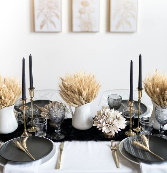 a bold Thanksgiving tablescape with a black runner and plates, black candles, wheat in jugs is very elegant