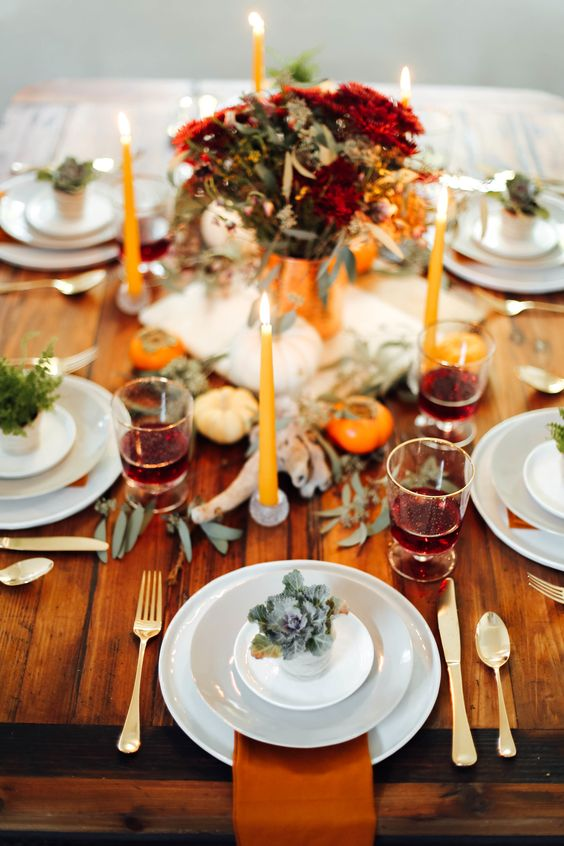 a bold modern Thanksgiving tablescape with bright blooms and candles, antlers, eucalyptus, white porcelain and rust napkins