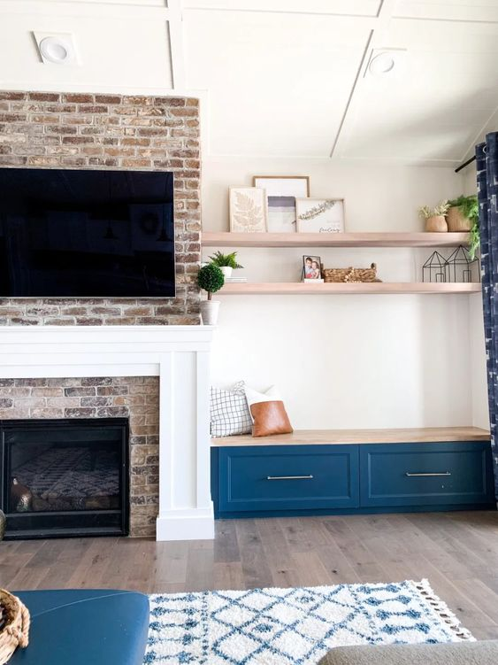 a brick clad fireplace with a built-in bench with drawers and some pillows plus built-in shelves over it