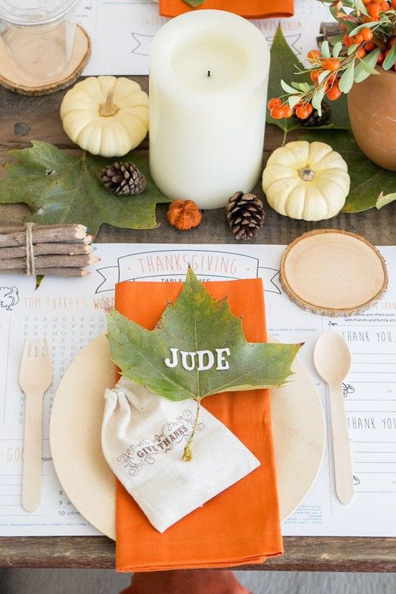 a bright and simple Thanksgiving table with fall leaves, berries, pumpkins, pillar candles and touches of orange