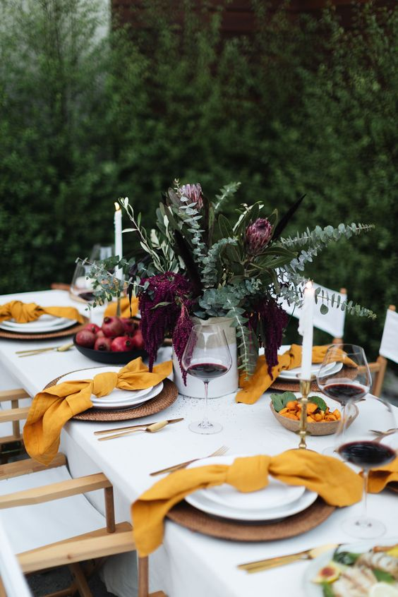 a bright modern Thanksgiving table with greenery and deep purple blooms, yellow napkins, woven chargers and gold cutlery rocks
