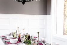 a bright modern Thanksgiving tablescape with a white runner, greenery and purple blooms, candles, purple napkins and white porcelain
