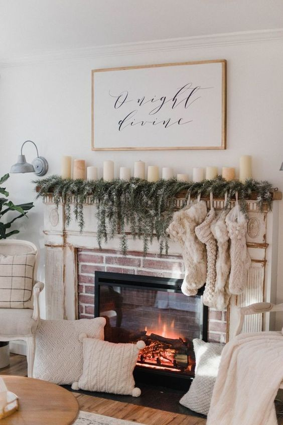 a built-in fireplace with an evergreen garland, lot sof stockings and pillar candles on the mantel