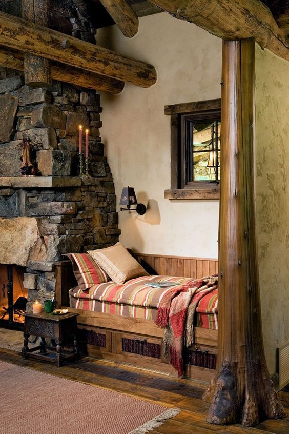 a chalet nook with a stone clad fireplace and a mantel, a built-in wooden bench with drawers and bright bedding is welcoming