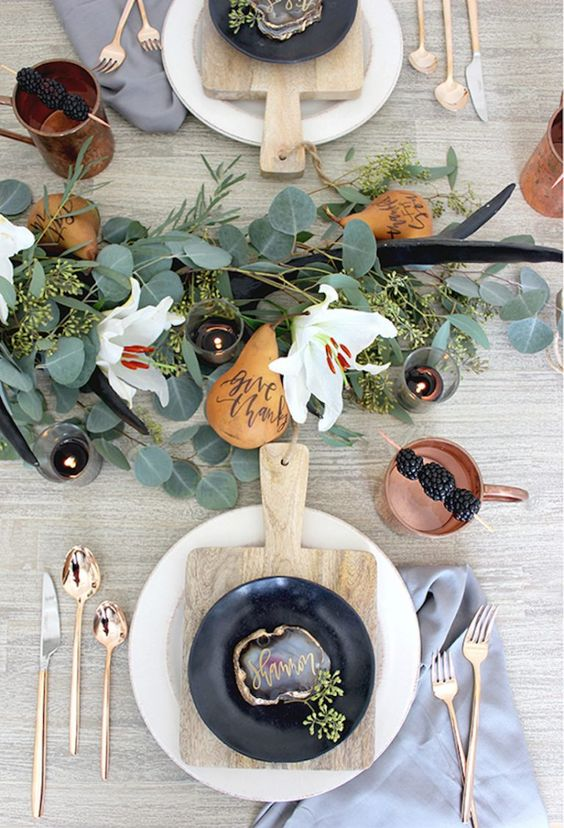 a chic modern Thanksgiving table with a greenery and white bloom runner, antlers, copper cutlery and mugs, wooden boards and agates