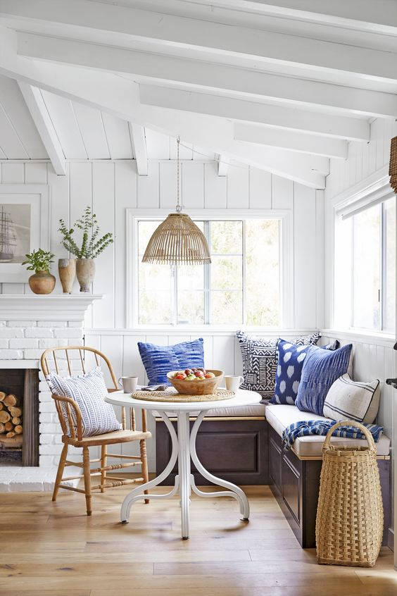 a coastal space with a white brick clad fireplace, a banquette corner seating, a round table and a wooden chair is welcoming