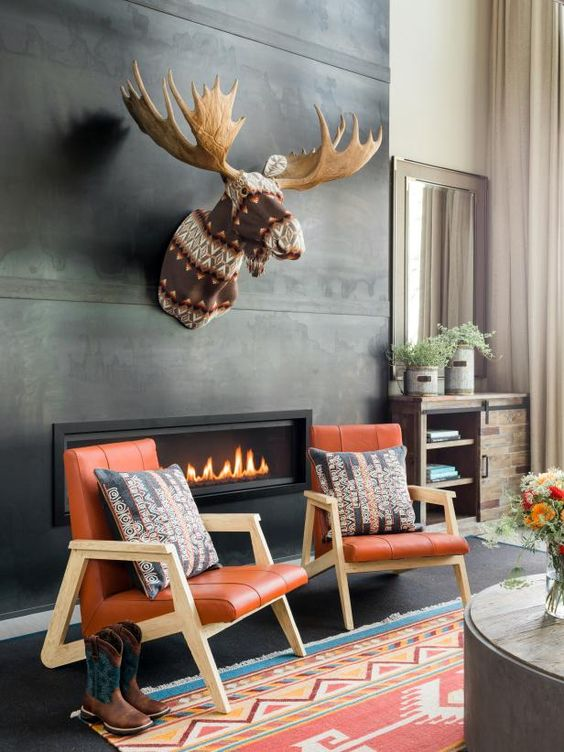 a contemporary fireplace nook with a concrete clad fireplace, a faux taxidermy piece, orange chairs and pillows plus cowboy boots