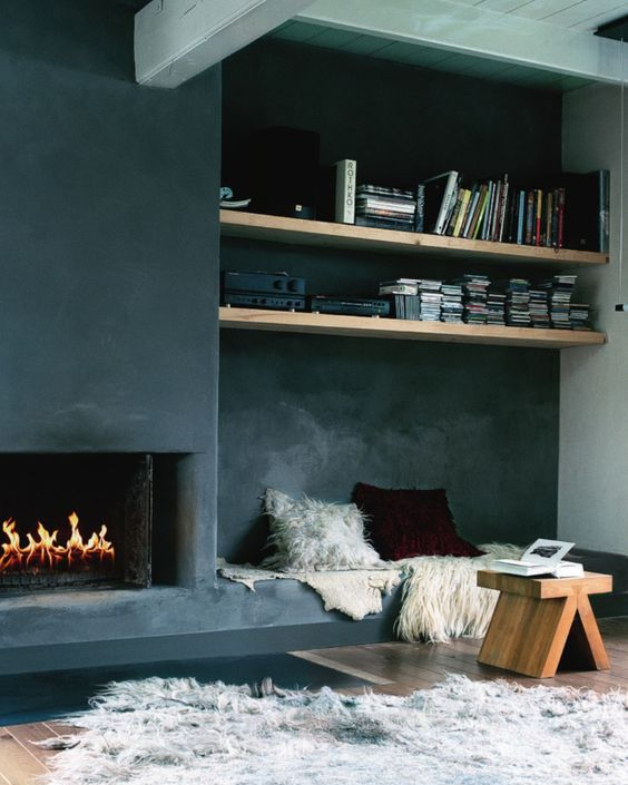 a contemporary space with a built-in fireplace with a screen and a bench with pillows built-in next to the fireplace