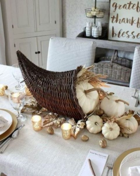 a cornucopia Thanksgiving centerpiece with white pumpkins, wheat and gold leaves plus nuts