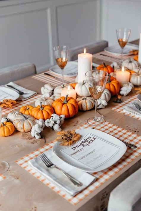 a cozy and bright fall centerpiece of white and orange pumpkins, pillar candles and cotton