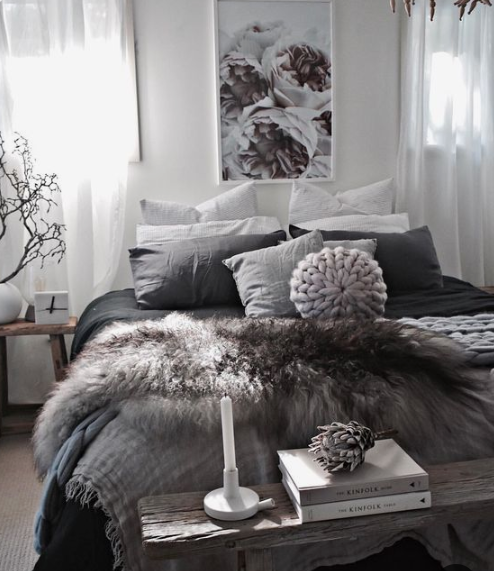 a cozy and moody bedroom with faux fur blankets, knit blankets and a rough wood bench is winter reayd and very trendy