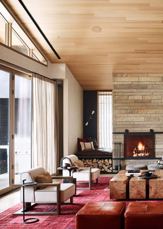 a cozy farmhouse space with a brick clad fireplace, a built-in seat with pillows and firewood storage