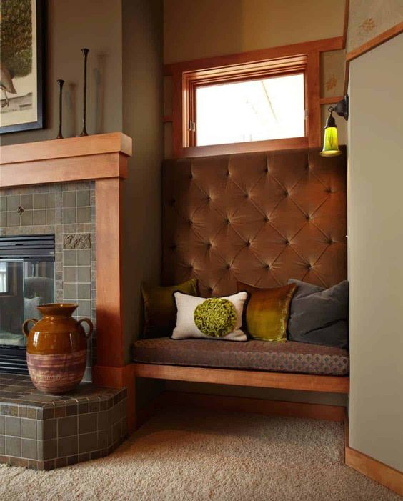 a cozy fireplace nook with a fireplace clad with green tiles and a built-in bench with pillows and a bold vase is cool