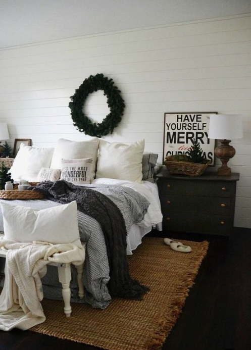 a cozy wintry bedroom with knit blankets, an evergreen wreath, a Christmas tree feels veyr cozy and chic