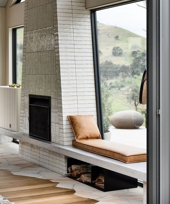 a creative modern fireplace clad with tiles, with a windowsill daybed with leather cushions and a firewood storage under it