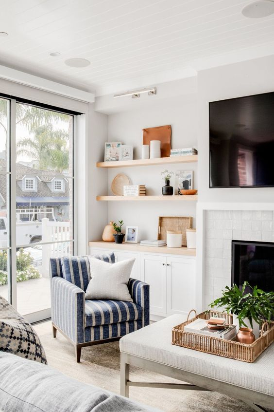 a farmhouse space wiht a white brick clad fireplace, built-in shelves and cabinets, a striped chair and a large ottoman and greenery