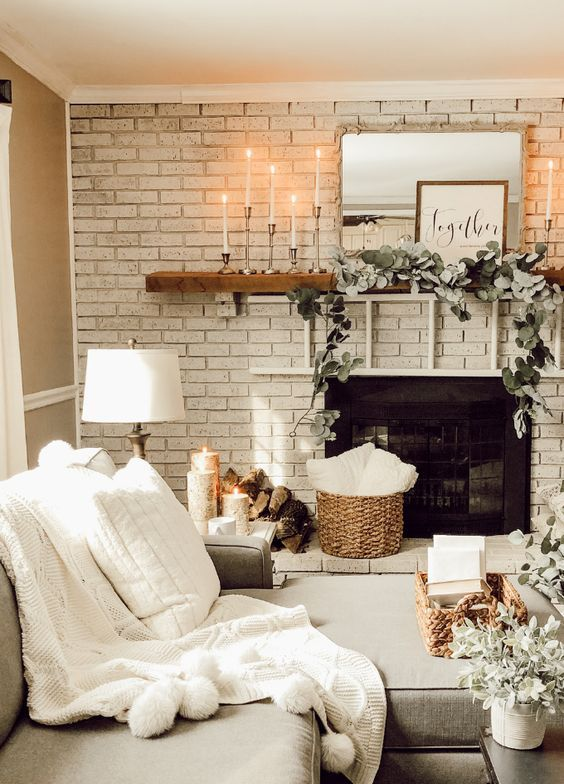 a fireplace deocrated with fresh greenery, candles and some firewood by its side for a cozy feel