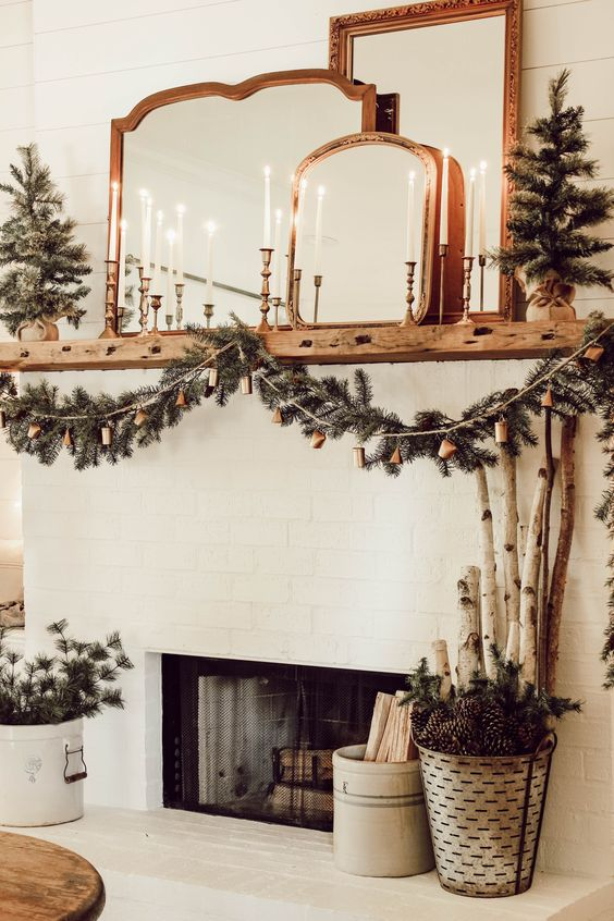 a fireplace styled with an evergreen garland with bells, lot sof candles and lots of mirrors