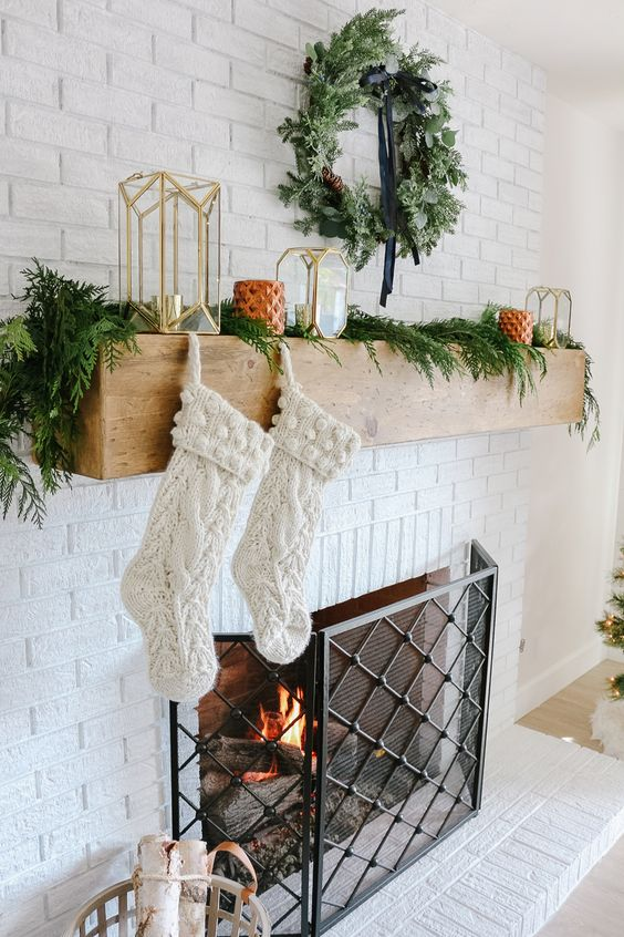 a fireplace styled with evergreens, an evergrene wreath and candle lanterns plus stockings for a cool look