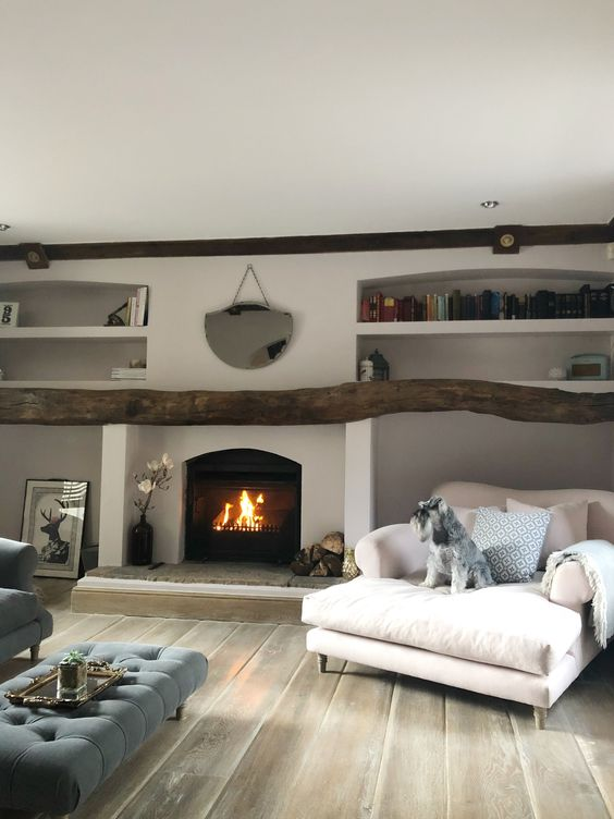 a fireplace with rocks covered with a rough log and a double lounger with pillows is a stylish and welcoming idea