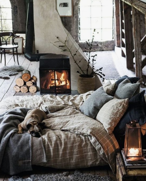 a gorgeous winter bedroom with plaid and knit bedding, a fur rug, a hearth and some firewood that make the space cozy