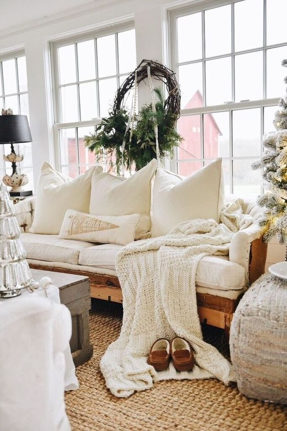 a knit blanket and lots of pillows plus a jute rug make the living room welcoming and cozy