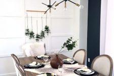 a laconic Thanksgiving tablescape with a eucalyptus arrangement, little white pumpkins, black plates and a fau fur runner