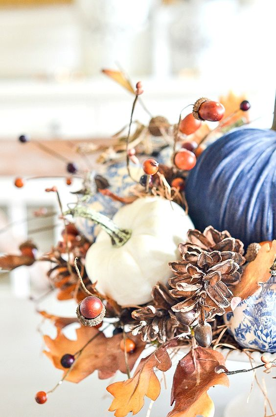 a lush Thanksgiving centerpiece of faux pumpkins, fall leaves berries, acorns and pinecones