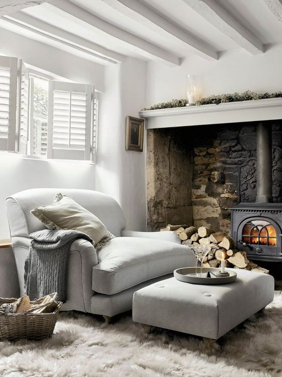 a metal hearth and firewood, a large double chair and a matching ottoman make up a welcoming and cool nook