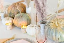 a modenr pastel Thanksgiving tablescape with pastel and gidled pumpkins, pastel pampas grass, pastel plates and gold cutlery