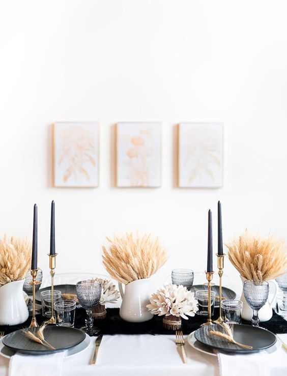 a modern Thanksgiving tablescape with a black runner, plates and tall candles, wheat arrangements and grey glasses