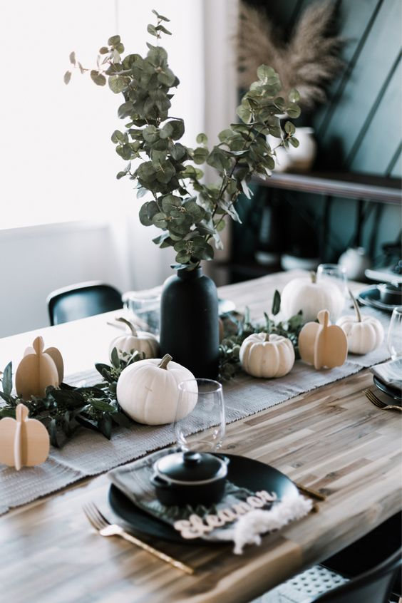 a modern Thanksgiving tablescape with a burlap runner, black plates and pots, pumpkins, greenery in a black vase is very chic