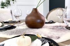 a modern Thanksgiving tablescape with a faux fur runner, black woven placemats, white porcelain and pumpkins, a brown vase with greenery