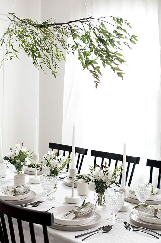 a modern and very neutral Thanksgiving tablescape with neutral porcelain and linens, greenery and white blooms plus white candles