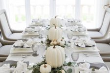 a modern elegant Thanksgiving tablescape with a greenery runner, white pumpkins, grey plates and glasses is very chic