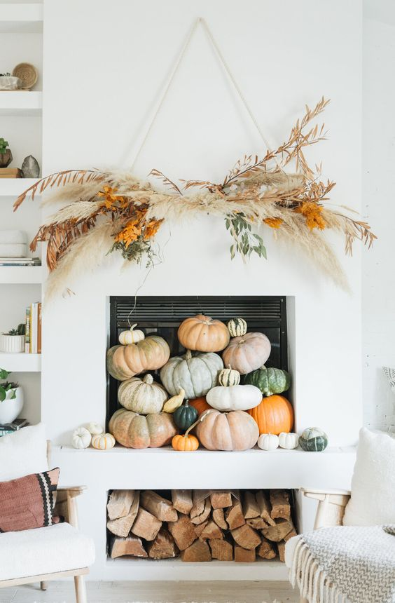a modern fall or Thanksgiving fireplace filled with various natural pumpkins, with a pampas grass and greenery overhead decoration