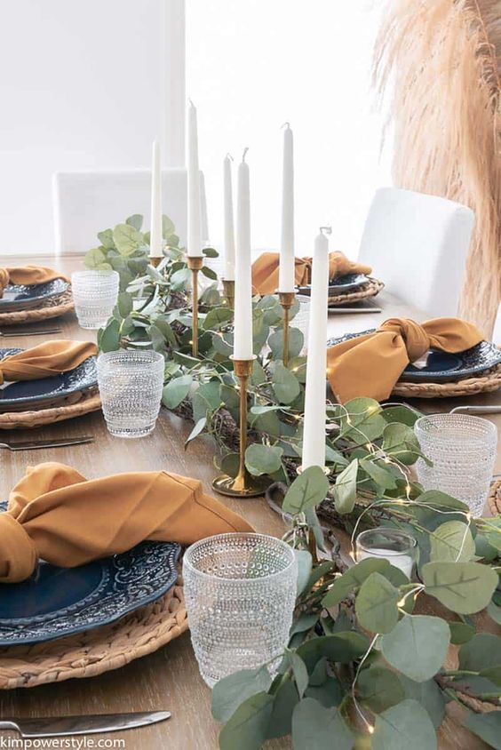 a modern farmhouse Thanksgiving tablescape with a greenery and light runner, candles, blue plates, woven chargers and terracotta napkins