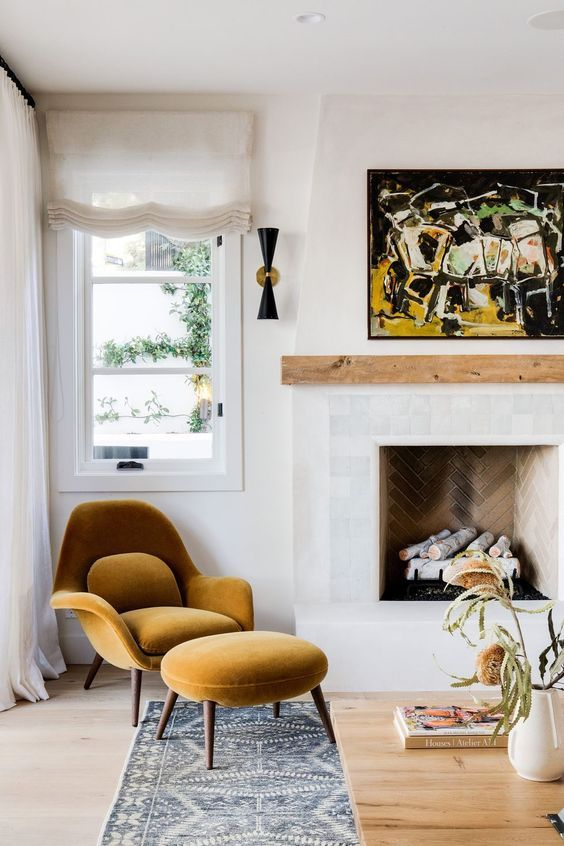 a modern nook with a brick clad fireplace, a wooden mantel, a mustard-colored chair with a footrest and a bold artwork for a chic look