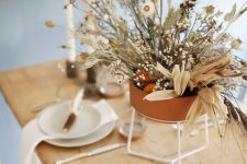 a modern organic Thanksgiving tablescape with white porcelain, greenery and a beautiful dried flower and herb centerpiece in a terracotta pot