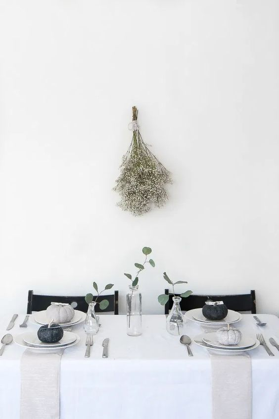 a modern to minimalist Thanksgiving tablescape with grey and black pumpkins, greenery and neutral linens is laconic and stylish