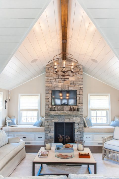a neutral chic space with a stone clad fireplace, two built-in benches with cushions and pillows plus a stone mantel