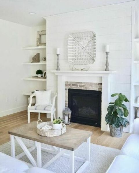 a neutral farmhouse fireplace nook with a brick clad fireplace, a white chair with a pillow is a welcoming space to spend time