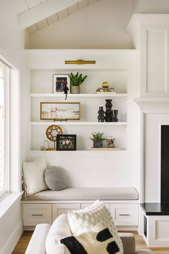 a neutral farmhouse nook with a chic built-in bench with pillows and built-in shelves over it next to the fireplace